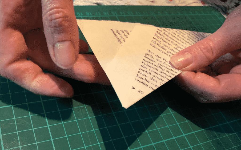 3. Falte: unten soll jetzt noch eine kleine Ecke überstehen, diese scharf über die Seite in das Buch reinfalten, damit halten die ersten beiden Falten